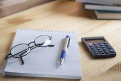 Miejsce pracy księgowy Notepad w pudełku z piórem, kalkulatorem i szkłami na drewnianym stole w tle sterta okrzyki niezadowolenia Zdjęcie Stock