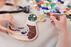 Miejsce pracy mozaika mistrz: kobiety ` s wręcza mienia narzędzie dla mozaika szczegółów w trakcie robić mozaice Obraz Stock