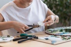 Miejsce pracy mozaika mistrz: kobiety ` s wręcza mienia narzędzie dla mozaika szczegółów w trakcie robić mozaice Obrazy Stock