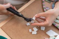 Miejsce pracy mozaika mistrz: kobiety ` s wręcza mienia narzędzie dla mozaika szczegółów w trakcie robić mozaice Zdjęcia Royalty Free