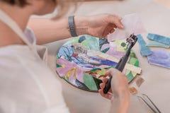 Miejsce pracy mozaika mistrz: kobiety ` s wręcza mienia narzędzie dla mozaika szczegółów w trakcie robić mozaice Fotografia Stock