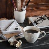 Miejsce pracy z biznesów przedmiotami książki, notatniki, pióra, pastylka, szkła, czekolada i filiżanka kawy -, i Fotografia Royalty Free