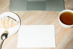 Miejsce pracy z laptopem, herbatą i croissant w domu, Odgórny widok Obrazy Stock