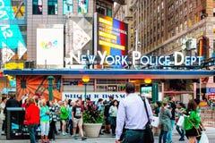 Miejscowi i turyści iść o ich biznesie w ruchliwie times square na zewnątrz NYPD times square dzielnicy Obraz Stock