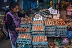 Miejscowi młodej kobiety sprzedawania jajka w stojaku obrazy royalty free