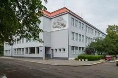 Miejski budynek z emblematem na ścianie z chorągwianym lataniem na ścianie z zielenią przycinał krzaki obok go i Zdjęcie Stock