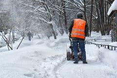 Miejski pracownik usuwa śnieg od Moscow ulicy używać śnieżną dmuchawę Fotografia Royalty Free