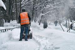 Miejski pracownik usuwa śnieg od Moscow ulicy używać śnieżną dmuchawę Zdjęcie Stock