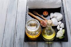 Miel, aceite del aroma, velas ardientes, brotes de flores y guijarros para el balneario y los procedimientos del aroma fotografía de archivo libre de regalías