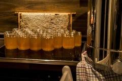 Miel amarilla de oro en el tarro de cristal en el marco de los comp del espacio de la copia del primer del tablero de madera llen Foto de archivo