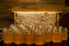 Miel amarilla de oro en el tarro de cristal en el marco de los comp del espacio de la copia del primer del tablero de madera llen Imagen de archivo libre de regalías