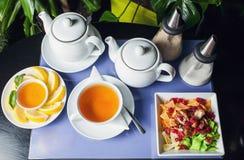 Miel avec les noix et la tasse de thé sur le pourpre Photographie stock libre de droits