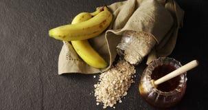 Miel, banane et farine d'avoine sur le fond noir 4k banque de vidéos