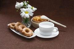 Miel, biscuits, tasse et un vase de marguerites Photographie stock libre de droits