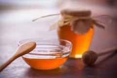 Miel con el cazo de madera de la miel en cuenco en la tabla Imágenes de archivo libres de regalías