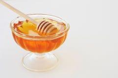 Miel con el cazo de madera de la miel en el tarro de cristal Fotos de archivo libres de regalías