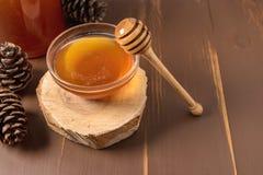 Miel con el cazo de madera de la miel en tarro Fotografía de archivo libre de regalías