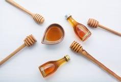 Miel con el cazo de madera y poca botella de la miel en de madera blanco Imagenes de archivo