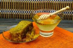 Miel con el panal en una placa de cristal en la tabla de madera vieja Fotografía de archivo