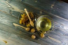 Miel con el panal en una placa de cristal en la tabla de madera vieja Foto de archivo libre de regalías
