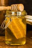 Miel con el peine de la miel en un tarro Foto de archivo