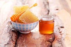 Miel con el peine de la miel Imagenes de archivo
