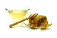 Miel con los panales en una placa de cristal aislada en un fondo blanco Imagenes de archivo