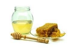 Miel con los panales en una placa de cristal aislada en un fondo blanco Foto de archivo libre de regalías