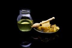 Miel con los panales en una placa de cristal aislada en un fondo negro Fotografía de archivo