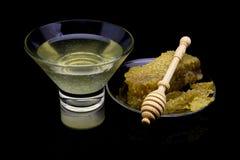 Miel con los panales en una placa de cristal aislada en un fondo negro Imagen de archivo libre de regalías