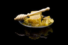 Miel con los panales en una placa de cristal aislada en un fondo negro Imágenes de archivo libres de regalías