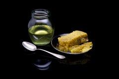 Miel con los panales en una placa de cristal aislada en un fondo negro Fotos de archivo libres de regalías