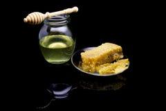 Miel con los panales en una placa de cristal aislada en un fondo negro Foto de archivo