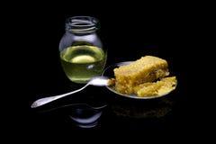 Miel con los panales en una placa de cristal aislada en un fondo negro Foto de archivo libre de regalías