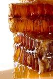 Miel découlant des nids d'abeilles sur le fond clair Image stock