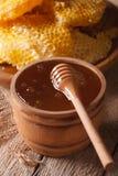 Miel d'or délicieux dans une cuvette en bois avec un bâton Photo libre de droits