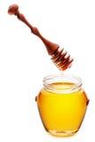 Miel d'or dans un pot avec du miel de versement de dispositif d'écoulement en bois de miel Images libres de droits
