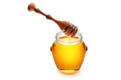 Miel d'or dans un pot avec du miel de versement de dispositif d'écoulement en bois de miel Images stock