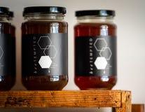 Miel dans des pots en verre avec les couvercles noirs à vendre sur des étagères de magasin faites à partir d'une vieille ruche d' images libres de droits