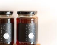 Miel dans des pots en verre avec les couvercles noirs à vendre sur des étagères de magasin images stock