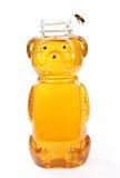 Miel dans la bouteille d'ours avec une abeille de vol Photo stock