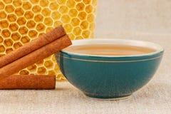 Miel dans la cuvette avec le nid d'abeilles et la cannelle Photographie stock