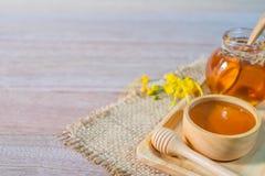 Miel dans le plongeur en bois de miel sur le sac photographie stock