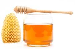Miel dans le pot avec le plongeur et le nid d'abeilles sur le fond d'isolement Photo libre de droits