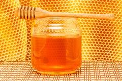 Miel dans le pot avec le plongeur et le nid d'abeilles sur le tapis Photographie stock libre de droits