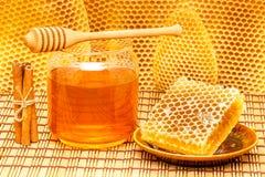 Miel dans le pot avec le plongeur, le nid d'abeilles et la cannelle o Photographie stock