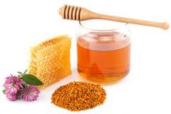 Miel dans le pot avec le plongeur, le nid d'abeilles, le pollen et les fleurs Photos stock
