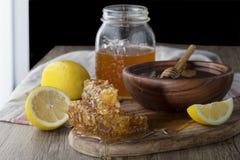 Miel dans le pot avec le nid d'abeilles et le drizzler en bois images libres de droits