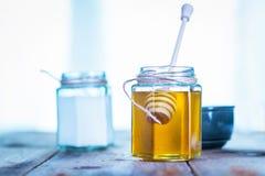 Miel dans un pot avec du yaourt derrière Photos libres de droits