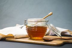 Miel dans un pot avec un plongeur en bois de miel sur un conseil en bois photos libres de droits